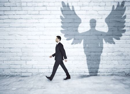 Walking businessman with angel shadow in brick interior