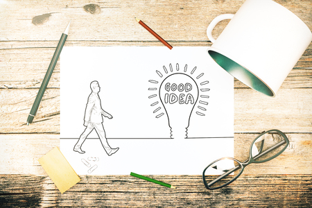 computer education: Top view of wooden desktop with iron mug, supplies, glasses and sketch of man and light bulb. Idea concept. 3D Rendering Stock Photo