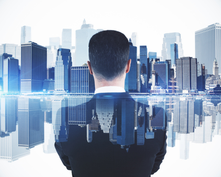 Back view of young businessman on abstract blue city background. Success concept. Double exposure