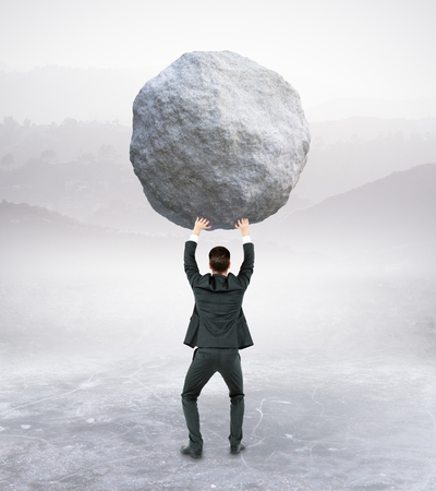 Back view of young businessman holding huge rock on abstract background. Struggle concept