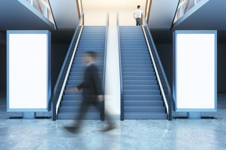 Side view of blurry businessman walking past escalators and blank billboards. Advertisement concept. Mock up, 3D Rendering