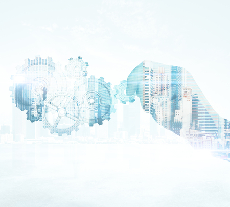 Close up of businessmans hand holding abstract cogs on city background. Success concept. Double exposure