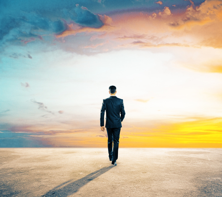 Back view of young businessman walking on concrete ground. Beautiful sky in the background. Forward concept Stock Photo