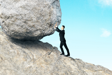 Side view of young businessman pushing huge rock up mountain. Beautiful background. Hard work concept Stock Photo
