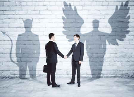 Businessmen with angel and demon shadows shaking hands in brick interior. Team work concept