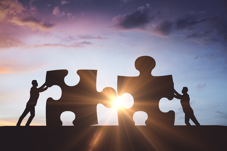 People silhouettes putting puzzle pieces together on beautiful sky background with sunlight. Partnership concept