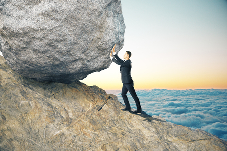 Side view of young businessman pushing huge rock up mountain. Beautiful background. Perseverance concept