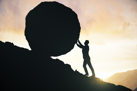 Side view of male silhouette pushing huge rock uphill. Beautiful sky background. Struggle concept