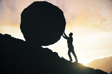 Zijaanzicht van mannelijk silhouet die enorme rots bergopwaarts duwen. Mooie hemelachtergrond. Strijdconcept Stockfoto