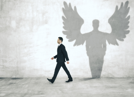 Walking man with angel shadow in concrete interior Stock Photo