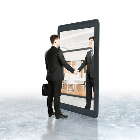pad: Businessman shaking hands with abstract partner inside tablet. White background. Digital business concept Stock Photo