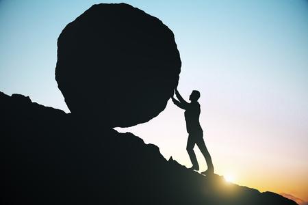 男性のサイドビューのシルエット上り坂の押すことの巨大な岩。美しい空を背景。難易度の概念 写真素材