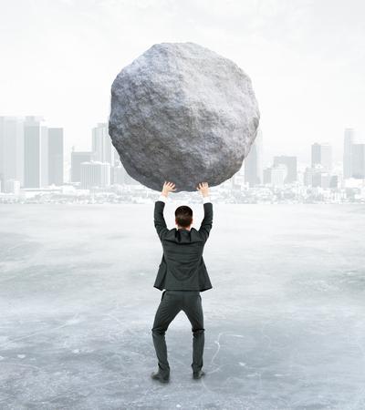 Achteraanzicht van jonge zakenman die enorme rots op abstracte achtergrond houdt. Burden concept