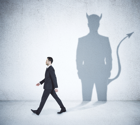 Walking businessman with devil shadow in concrete interior 版權商用圖片