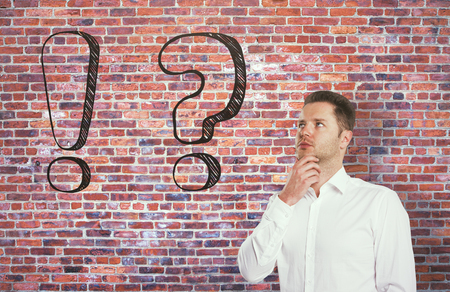 Thoughtful businessman with drawn question and exclamation marks on red brick background. Choice concept