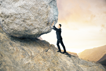 Side view of young businessman pushing huge rock up mountain. Beautiful background. Effort concept Stock Photo