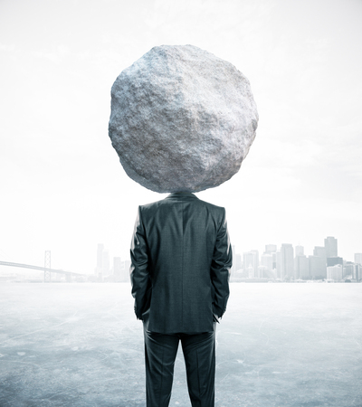 Back view of rock headed businessman on abstract background. Struggle concept
