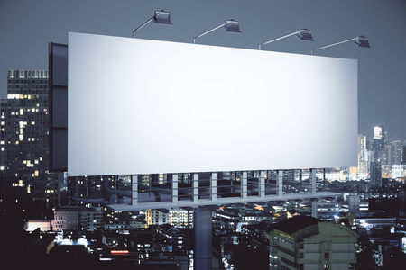 Side view of empty billboard on illuminated night city background. Advertisement concept. 3D Rendering Stock Photo