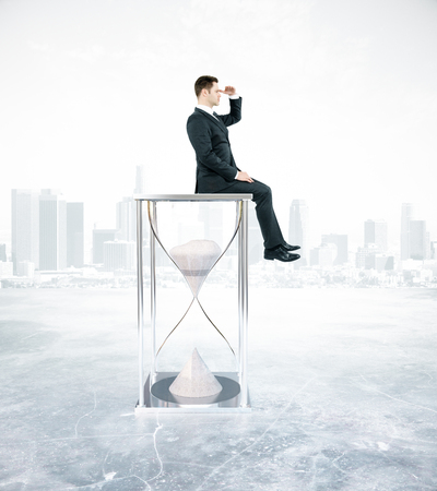 expanse: Side view of young businessman sitting on hourglass and looking into the distance. City background. Time management concept