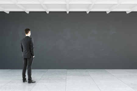 Side view of young businessman looking at empty wall in interior. Mock up, 3D Rendering Stock Photo