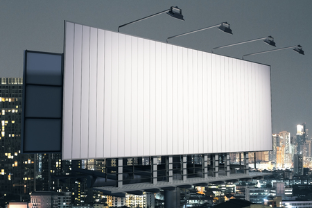 Side view of empty billboard on illuminated night city background. Commerce concept. 3D Rendering Stock Photo