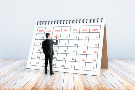 Young man writing in calendar placed on wooden surface. Schedule concept. 3D Rendering