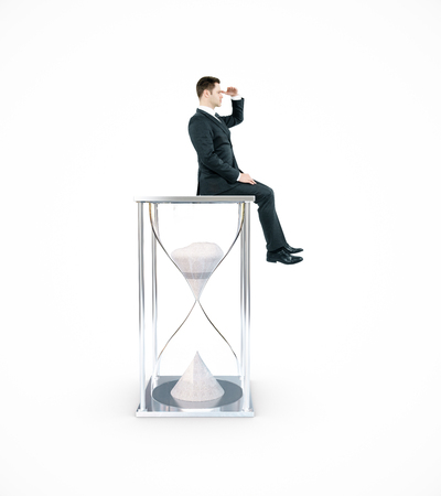 Side view of young businessman sitting on hourglass and looking into the distance. Whiite background. Time management concept