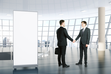 Uomini d'affari che agitano le mani in interno con stand vuoto dell'annuncio e vista panoramica della città. Concetto di lavoro di squadra. Mock up, rendering 3D Archivio Fotografico - 78063016