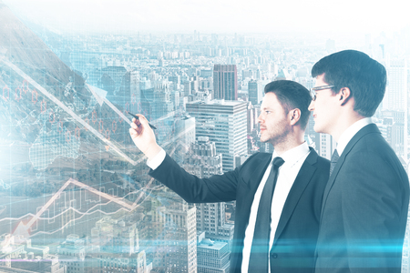 flèche double: Side view of two handsome young businessmen drawing forex chart on abstract city background. Fund management concept. Double exposure