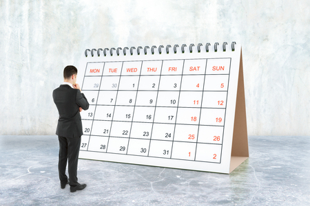 Thoughtful young businessman looking at calendar placed on concrete surface. Schedule concept. 3D Rendering Stock Photo