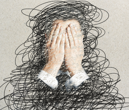 Young businessman covering face with hands. Abstract background with scribble. Stress concept