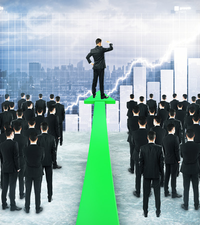 Businessman standing on green chart arrow and looking into the distance on city background. Research concept 版權商用圖片