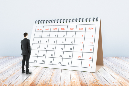 Thoughtful young man looking at calendar placed on wooden surface. Schedule concept. 3D Rendering