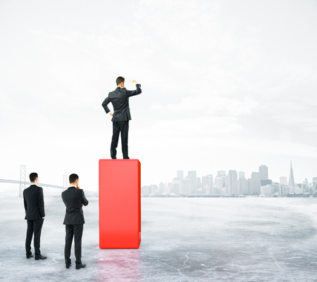 Businessman standing on abstract red pedestal on city background and looking into the distance. Leadership concept 版權商用圖片