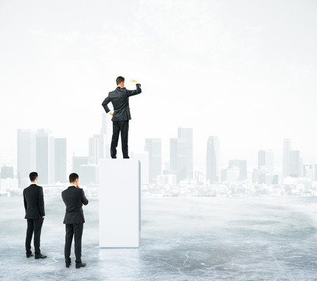 Businessman standing on abstract grey pedestal on city background and looking into the distance. Leadership concept