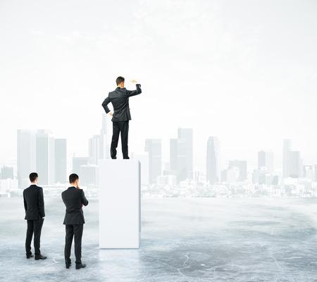Homme d'affaires debout sur le socle gris abstrait sur le fond de la ville et regarder dans la distance. Concept de leadership Banque d'images - 78680023