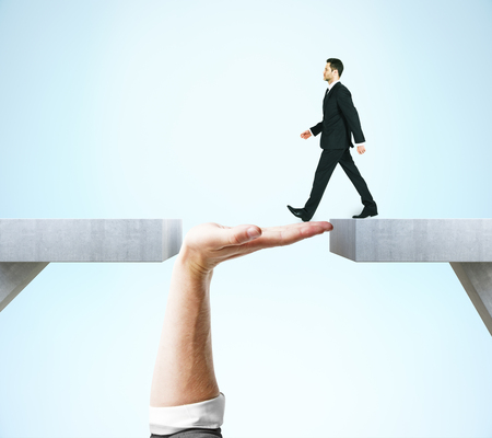 Businessman crossing abstract hand bridge on blue background. Teamwork concept