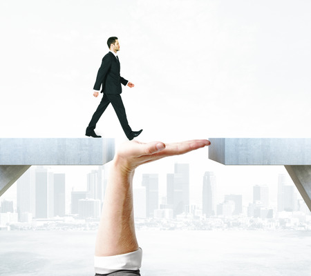 Businessman crossing abstract hand bridge on city background. Support concept
