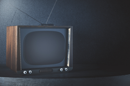 Close up of obsolete TV placed on grey table. Concrete wall background. Mock up, 3D Rendering Reklamní fotografie