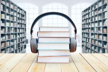 本棚の背景にヘッドフォン本杭。3 D レンダリング。オーディオ ブックのコンセプト