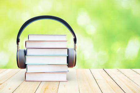 緑の背景の上にヘッドフォンと本スタック。3 D レンダリング。オーディオ ブックのコンセプト