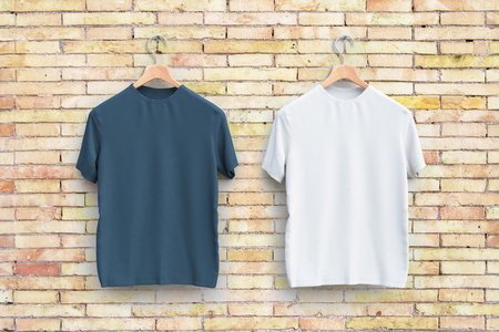 Hangers with empty grey and white t-shirts hanging on brick wall. Apparel concept Stock Photo