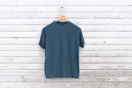 Hanger with empty grey shirt hanging on wooden wall. Retail concept Stockfoto
