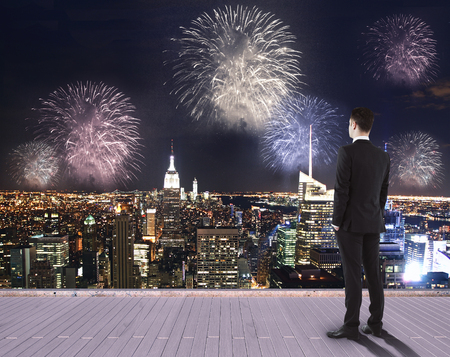 Young businessman on pier looking at night city with fireworks. Holiday concept Stock Photo