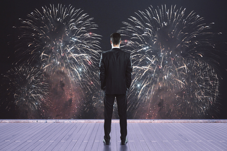Back view of young businessman on wooden pier watching fireworks. Celebration concept
