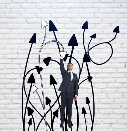 Abstract image of young man hanging on tangled arrows. Brick background. Choice concept