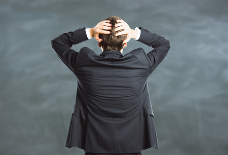 Back view of stressed young businessman on blackboard background. Stress concept