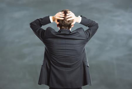 Vista posteriore di giovane uomo d & # 39 ; affari sollecitato su sfondo lavagna. concetto di stress Archivio Fotografico - 79634329
