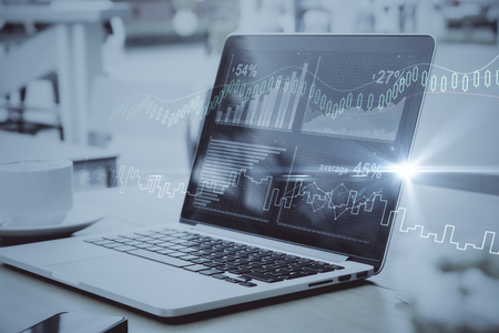 Side view of laptop with digital business charts placed on desktop with coffee cup. Toned image. Finance concept
