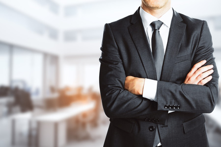 Businessman with folded arms on blurry interior background. Confidence concept. 3D Rendering